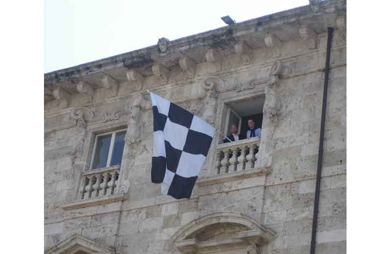 Castelli e Brugni espongono il bandierone da Palazzo Arengo