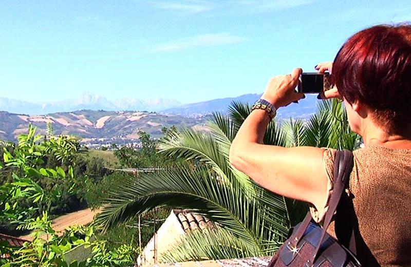 Un turista fotografa il panorama in una gita di Vivendo il Piceno in percorsi sorsi e morsi