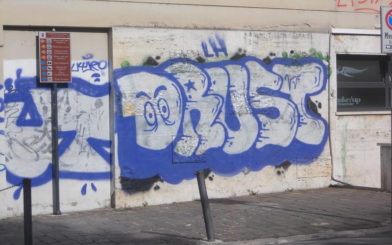 La firma del tagger su un muro di viale De Gasperi