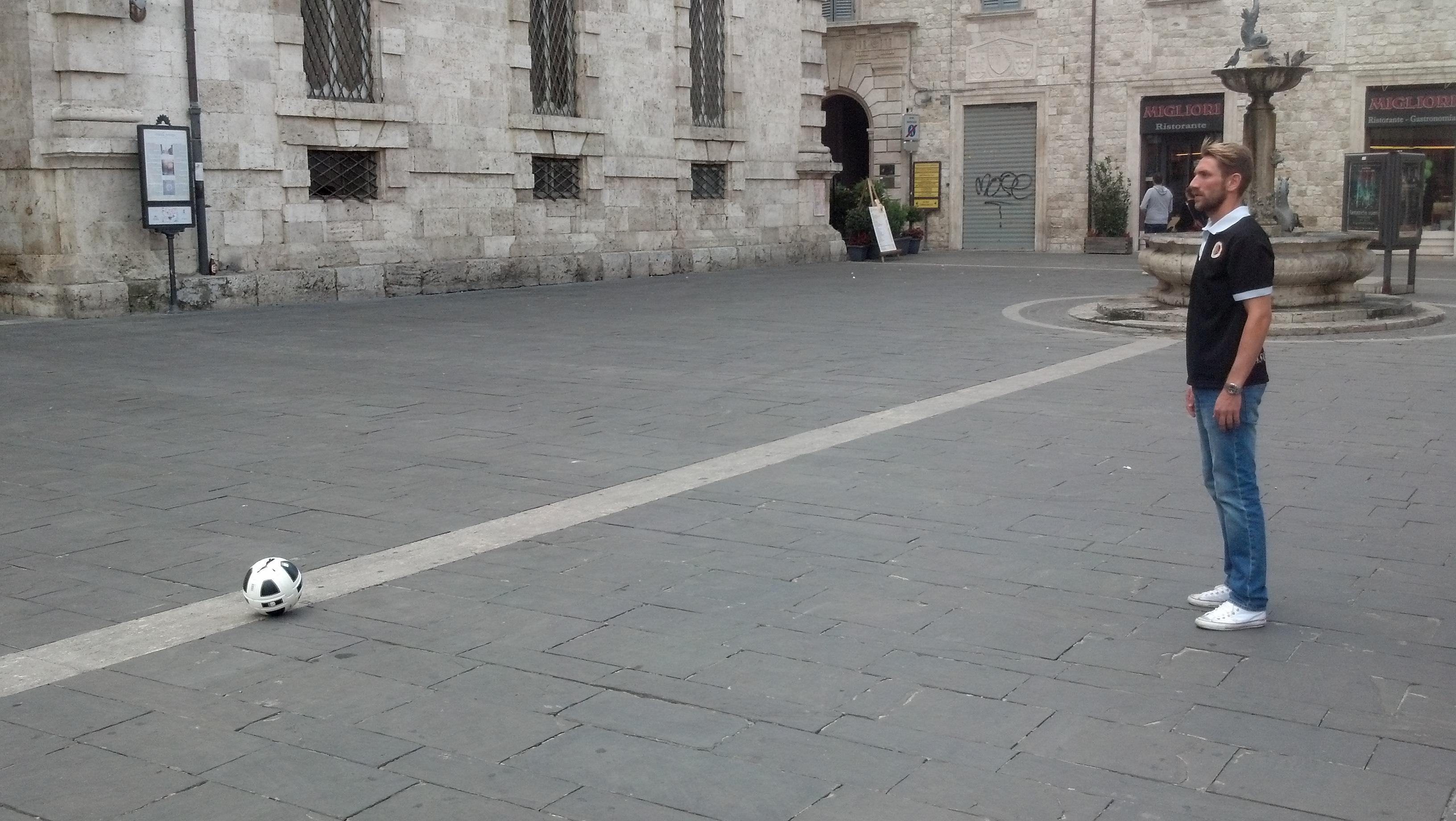 Massimo Loviso in piazza Arringo mentre calcia il pallone verso Soncin per lo spot dell'Ascoli Calcio in merito al lancio della tv della società calcistica