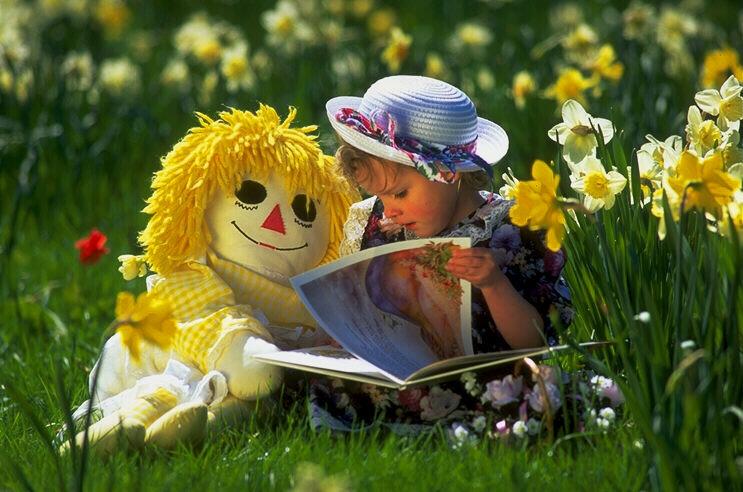 Bambina che legge in un parco